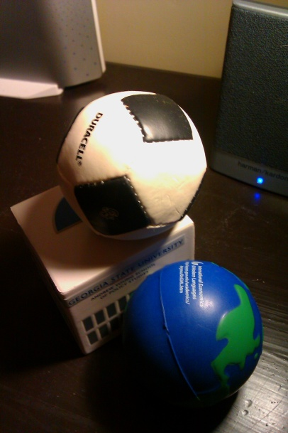 juggling implements: globe, soccer ball, miniature building